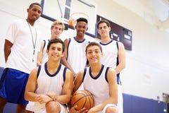 Μέλη του αρσενικού ομάδα μπάσκετ γυμνασίου με το λεωφορείο στοκ εικόνα