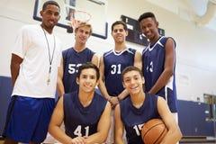 Μέλη του αρσενικού ομάδα μπάσκετ γυμνασίου με το λεωφορείο στοκ εικόνες