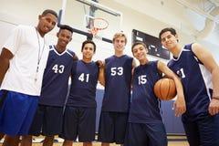 Μέλη του αρσενικού ομάδα μπάσκετ γυμνασίου με το λεωφορείο στοκ εικόνες με δικαίωμα ελεύθερης χρήσης