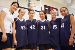 Μέλη του θηλυκού ομάδα μπάσκετ γυμνασίου με το λεωφορείο στοκ φωτογραφία