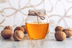Μέλι και ξύλα καρυδιάς Μέλι με τα καρύδια στον ξύλινο άσπρο πίνακα Όμορφη ανασκόπηση Στοκ Εικόνες