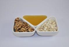 Μέλι, καρύδια, oatmeal για το πρόγευμα Στοκ Φωτογραφία
