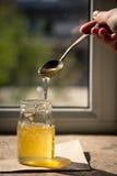 Μέλι που στάζει από ένα κουτάλι Οργανικό καθαρό μέλι στο βάζο στοκ εικόνα