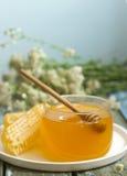 Μέλι σε ένα βάζο γυαλιού και μέλι στις κηρήθρες σε ένα παλαιό ξύλινο υπόβαθρο Στοκ εικόνες με δικαίωμα ελεύθερης χρήσης
