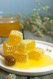 Μέλι σε ένα βάζο γυαλιού και μέλι στις κηρήθρες σε ένα παλαιό ξύλινο υπόβαθρο Στοκ Φωτογραφία