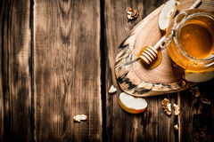 Μέλι σε ένα βάζο με τα καρύδια και τις φέτες της Apple Στοκ Φωτογραφία