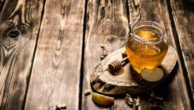 Μέλι σε ένα βάζο με τα καρύδια και τις φέτες της Apple Στοκ φωτογραφία με δικαίωμα ελεύθερης χρήσης