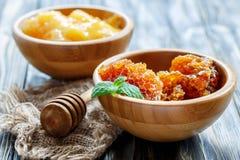 Μέλι στα ξύλινα κύπελλα και dipper για το μέλι Στοκ Εικόνες