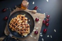 Μέλι στις βάφλες με τα μούρα κερασιών στο σκοτεινό ξύλινο υπόβαθρο Στοκ Εικόνα