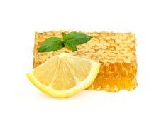 Μέλι στις κηρήθρες με το λεμόνι και τη μέντα. Στοκ Φωτογραφία