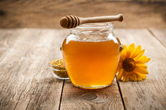 Μέλι στο βάζο γυαλιού στο ξύλινο υπόβαθρο στοκ φωτογραφία με δικαίωμα ελεύθερης χρήσης