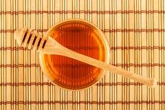 Μέλι στο βάζο με dipper στο χαλί Στοκ εικόνα με δικαίωμα ελεύθερης χρήσης