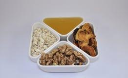 Μέλι, oatmeal, καρύδια, ξηρά - φρούτα για τη διατροφή Στοκ Φωτογραφία