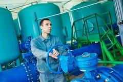 Μέλος των ενόπλων δυνάμεων που ενεργοποιεί το βιομηχανικό εξοπλισμό καθαρισμού ή διήθησης νερού στοκ φωτογραφία με δικαίωμα ελεύθερης χρήσης