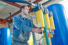 Μέλος των ενόπλων δυνάμεων που ενεργοποιεί το βιομηχανικό εξοπλισμό καθαρισμού ή διήθησης νερού στοκ φωτογραφία