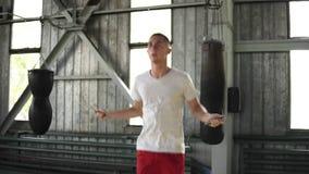 Μήκος σε πόδηα ενός καυκάσιου ατόμου στην άσπρη μπλούζα και κόκκινο σκληρά στη γυμναστική εγκιβωτισμού Επιμελώς ασκώντας με το άλ απόθεμα βίντεο