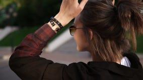 Μήκος σε πόδηα καταδίωξης ενός νέου κοριτσιού που περπατά υπαίθρια στην οδό ή το πάρκο Εύθυμος και ευτυχής Παραγωγή ενός ponytail απόθεμα βίντεο