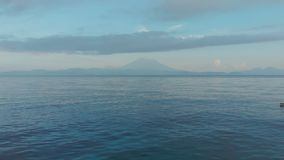 Μήκος σε πόδηα κηφήνων που πετά χαμηλά πέρα από τα κύματα της θάλασσας ενάντια στο σκηνικό του ηφαιστείου Agung πρεσών Ινδονησία φιλμ μικρού μήκους