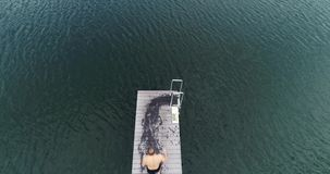 Μήκος σε πόδηα κηφήνων τριών καλά εκπαιδευμένων ανθρώπων που πηδούν στο νερό, υπαίθριο το πρωί απόθεμα βίντεο