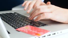 Μήκος σε πόδηα κινηματογραφήσεων σε πρώτο πλάνο 4k της νέας γυναίκας που χρησιμοποιεί την πιστωτική κάρτα εργαζόμενης στο lap-top απόθεμα βίντεο