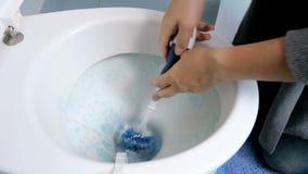 Μήκος σε πόδηα κινηματογραφήσεων σε πρώτο πλάνο 4k της νέας νοικοκυράς που καθαρίζει τη βρώμικη τουαλέτα με τη βούρτσα και το μέσ φιλμ μικρού μήκους