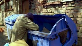 Μήκος σε πόδηα με το άστεγο άτομο που ψάχνει τα τρόφιμα και τα κενά μπουκάλια στα απορρίματα απόθεμα βίντεο