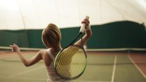Μήκος σε πόδηα πίσω πλευρών ενός ενεργού θηλυκού τενίστα που χτυπά τη σφαίρα με τη ρακέτα στο γήπεδο αντισφαίρισης Στο εσωτερικό, απόθεμα βίντεο