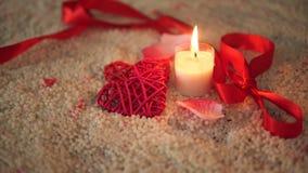 Μήκος σε πόδηα της ημέρας βαλεντίνων διακοσμήσεων, κορδέλλα και κάψιμο κεριών στην άμμο απόθεμα βίντεο