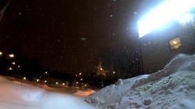 Μήκος σε πόδηα χιονοπτώσεων 4k από το σκοτεινό ουρανό με φωτισμένο το φως υπόβαθρο απόθεμα βίντεο