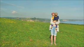Μήκος σε πόδηα Blured του νέου mom που περπατά με τον όμορφο γιο της στον πράσινο τομέα στην ήπια ηλιόλουστη ημέρα απόθεμα βίντεο