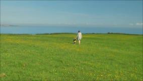 Μήκος σε πόδηα Blured του νέου mom που περπατά με τον όμορφο γιο της στον πράσινο τομέα στην ήπια ηλιόλουστη ημέρα φιλμ μικρού μήκους