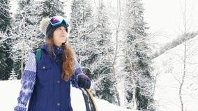 Μήκος σε πόδηα της περιπέτειας γυναικών snowboarder, που περπατά στα χιονώδη βουνά ορών φιλμ μικρού μήκους
