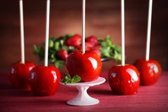 Μήλα καραμελών στον κόκκινο πίνακα στοκ εικόνα