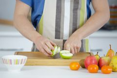 Μήλα που κόβονται στο άσπρο πιάτο στον ξύλινο πίνακα Στοκ Εικόνα