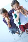 μήλα που τρώνε τα κορίτσια δύο στοκ φωτογραφία