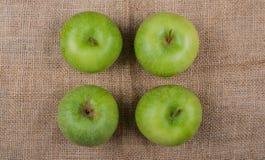 Μήλα που φωτογραφίζονται σε ένα ύφασμα γιούτας στοκ εικόνες