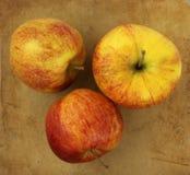 Μήλα σε ένα παλαιό αγροτικό τεμαχίζοντας χαρτόνι πετρών στοκ φωτογραφίες