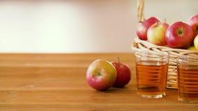 Μήλα στο καλάθι και τα ποτήρια του χυμού στον πίνακα απόθεμα βίντεο