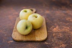 μήλα φρέσκα Άσπρη έκχυση ποικιλίας σε έναν ξύλινο τέμνοντα πίνακα Στοκ Φωτογραφία