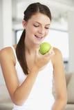 μήλο που τρώει τις νεολαίες γυναικών Στοκ Φωτογραφία