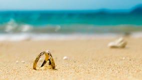 Μήνας του μέλιτος στο τροπικό νησί, δύο γαμήλια δαχτυλίδια στην αμμώδη παραλία Στοκ εικόνες με δικαίωμα ελεύθερης χρήσης