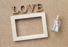 Μήνυμα αγάπης, μπουκάλι μηνυμάτων και ξύλινο πλαίσιο με το κείμενο αγάπης Στοκ Φωτογραφίες