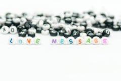 Μήνυμα αγάπης που γράφεται με τις χρωματισμένες επιστολές και τη γραπτή επιστολή στο υπόβαθρο στην άσπρη φωτογραφία έννοιας Στοκ φωτογραφία με δικαίωμα ελεύθερης χρήσης
