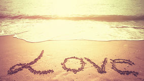 Μήνυμα ΑΓΑΠΗΣ που γράφεται στην άμμο μιας παραλίας στο χρόνο πρωινού Στοκ εικόνα με δικαίωμα ελεύθερης χρήσης