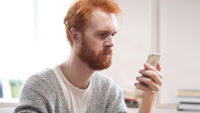 Μήνυμα ανάγνωσης σε Smartphone, άτομο με τις κόκκινες τρίχες Στοκ Φωτογραφίες