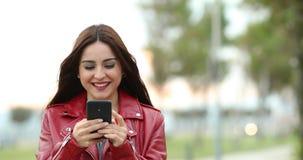 Μήνυμα γυναικών με ένα έξυπνο τηλέφωνο σε ένα πάρκο φιλμ μικρού μήκους