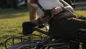Μήνυμα δακτυλογράφησης γυναικών ποδηλάτων στο κινητό τηλέφωνο στο θερινό πάρκο απόθεμα βίντεο