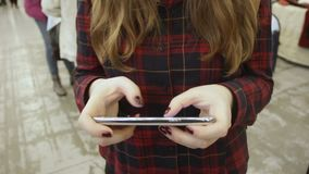 Μήνυμα δακτυλογράφησης κοριτσιών στη συσκευή της, που χρησιμοποιεί την κινητή εφαρμογή στη λεωφόρο αγορών απόθεμα βίντεο