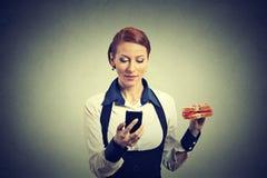 Μήνυμα ειδήσεων ανάγνωσης επιχειρησιακών γυναικών στην έξυπνη τηλεφωνική εκμετάλλευση που τρώει το σάντουιτς Στοκ Φωτογραφίες