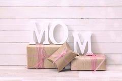 Μήνυμα ημέρας μητέρων με τα κιβώτια δώρων πέρα από το λευκό ξύλινο πίνακα Στοκ Εικόνα